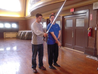 Greg teaches Mike how to swing the sword